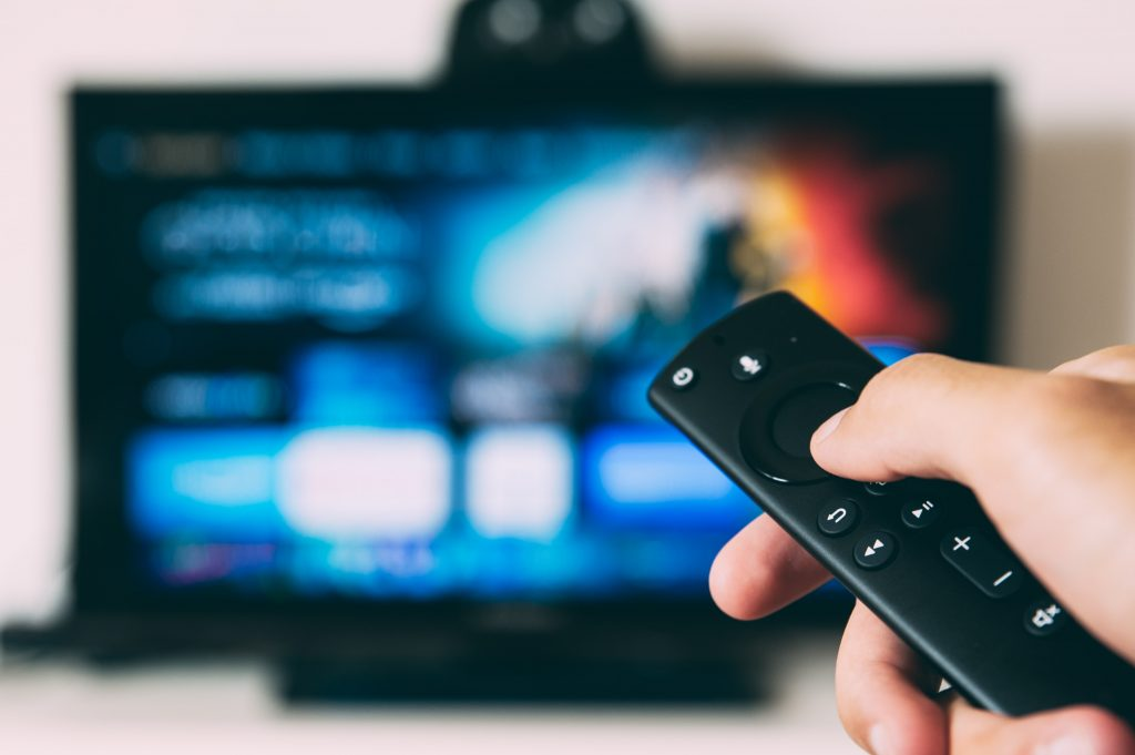 A person accessing Tv with the remote